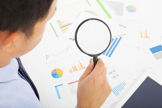 Businessman looking through magnifier glass to documents