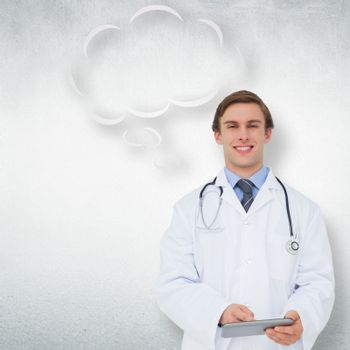 Young doctor using tablet pc with thought bubble against white wall