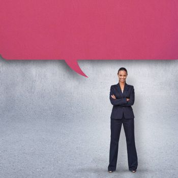 Confident businesswoman with speech bubble against grey wall