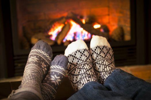 Feet in wool socks warming by cozy fire