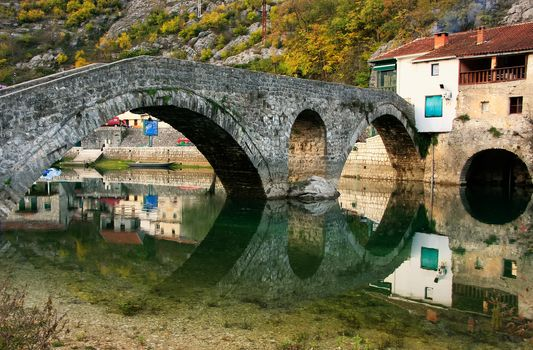 Arched bridge reflected in Crnojevica river, Montenegro