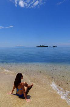 Young woman in bikini sitting on a beach, Vanua Levu island, Fij