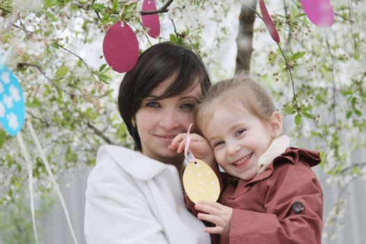 Happy mother and daughter in blooming garden decorating for Easter
