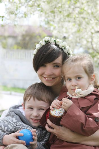 Happy mother and two children with Easter cake hugging among blooming garden