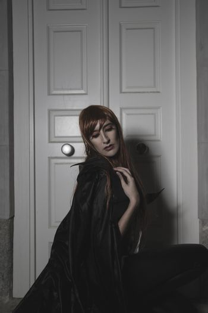 Dark beauty under rain, red hair woman with long black coat