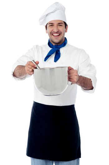 Smiling male cook holding a saucepan and ladle