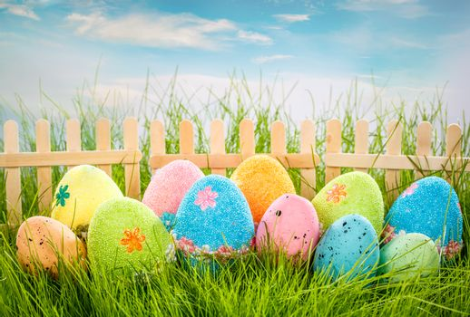 Decorated easter eggs in the grass on blue sky background