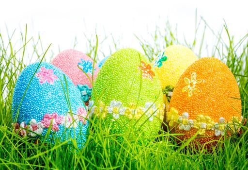 Decorated easter eggs in the grass on white background