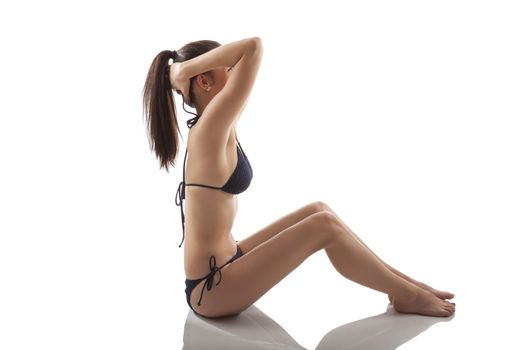 Sports and Fitness. Attractive sexy woman in bikini sitting and stretching isolated on white background.