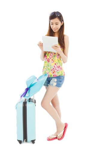 happy woman using tablet or ipad with  travel baggage