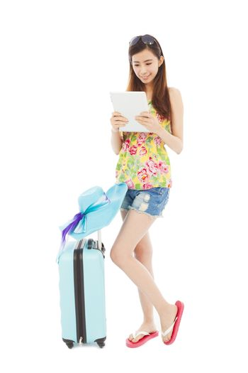 happy woman looking tablet or ipad with  travel baggage