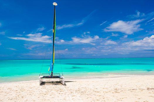Catamaran with colorful sail on caribbean beach