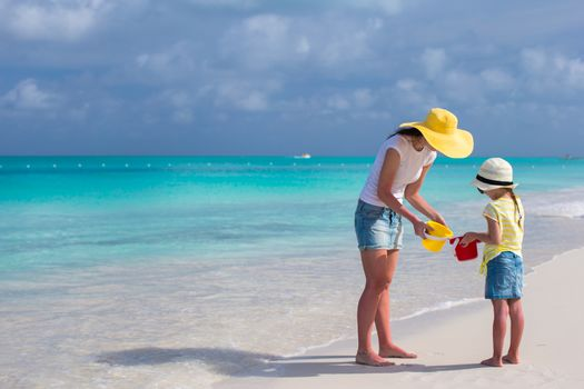 Mother and little daughter on the beach during their carribean vacation