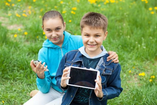 brother and sister with tablet PC and telephone