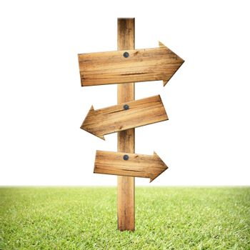 Wooden signpost of dark planks on lawn and white background.