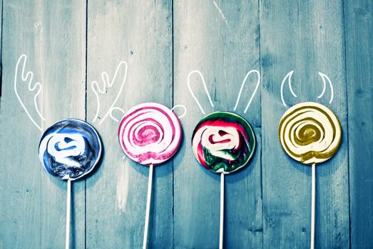 Photo of 4 lollipops with painted ears on wooden