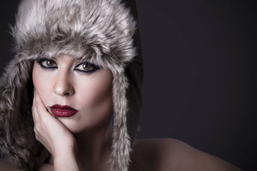 Woman frustrated with fur hat, winter concept
