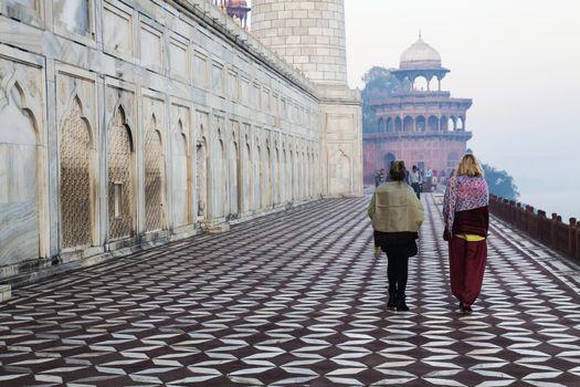 Taj Mahal, India,11Feb2014.Two Unknown adult women walking by Taj Mahal.