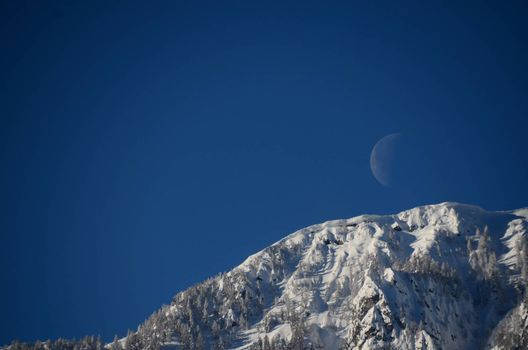 moon on blue sky with snow covered mountain