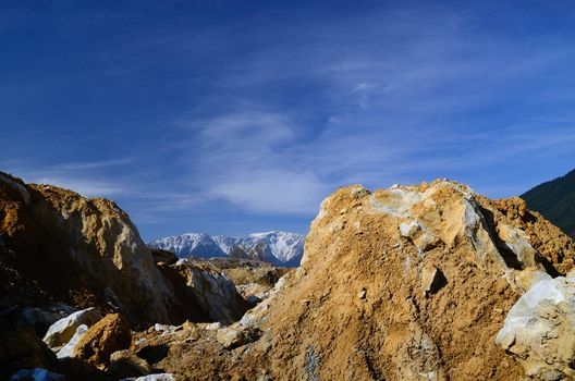 large quarry in the mountains with snow mountain in the background