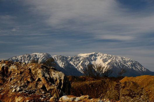 large quarry with mountains and snow in the background