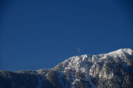 high mountain with fresh snow and moon on the sky in winter