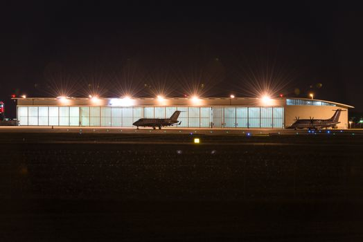 Two private jets parked in front of a lit hangar at dusk