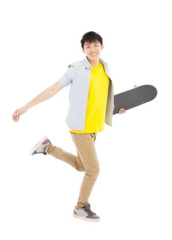 Vibrant young man holding a skateboard and walking