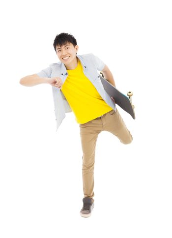 Vibrant young man holding a skateboard and make a pose