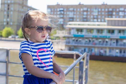 Little girl on the deck of a ship sailing in the big city