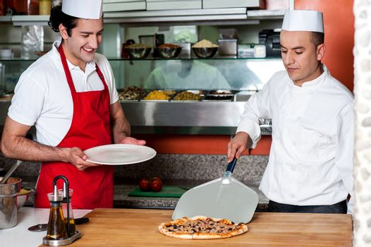 Chef picking pizza, ready to be served