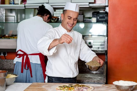 Chef busy in process of preparing pizza