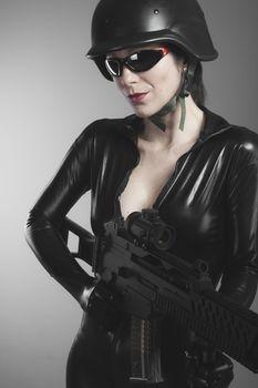 Brunette woman with enormous bulletproof vest and gun