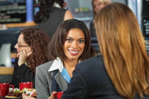 Smiling Black woman with coworker in cafeteria
