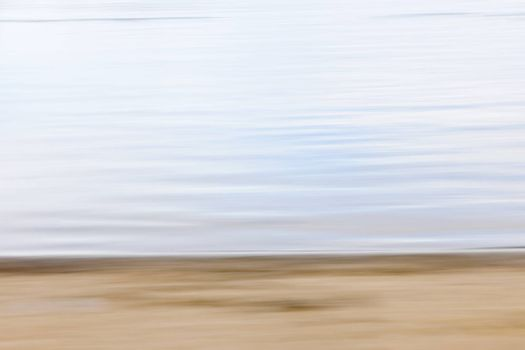 Background image of sand and water created by horizontal in-camera motion blur