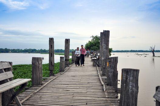 AMARAPURA,BURMA,October 9, 2013 : Unidentified people wear longi, Burmese traditional clothes in U Bein bridge on October 9,2013 in Amarapura,Burma.U Bein bridge is the oldest, longest teakwood bridge in the world