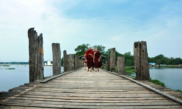 MANDALAY, MYANMAR - OCT 9: Unidentified young monks walking on U Bein Bridge, Myanmar. The bridge was built around 1850 and is believed to be longest teakwood bridge in the world. On October 9, 2013.