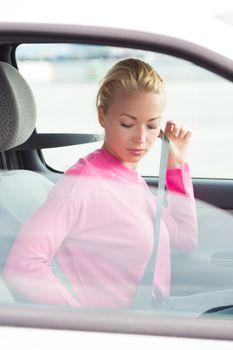 Beautiful woman fastening seat belt.
