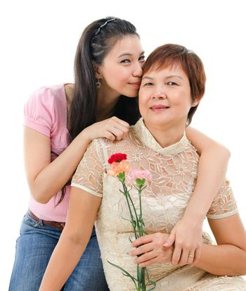 Senior mother holding carnation flower, adult daughter embraces and kissing mom, isolated on white background. Mixed race Asian family portrait.