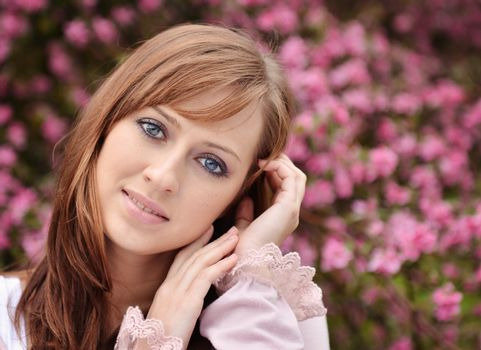 Beautiful girl posing over spring flowers background
