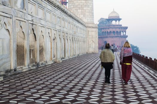 Agra, India, 11February2014. Rearview Unknown Two adult women walking by Taj Mahal.