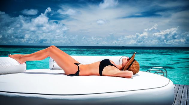 Sexy model with perfect body lying down on big white lounger on the beach and taking sunbath, luxury summer holidays, pleasure and enjoyment concept