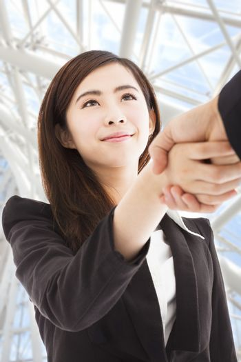 smiling business woman shaking hands in the office building