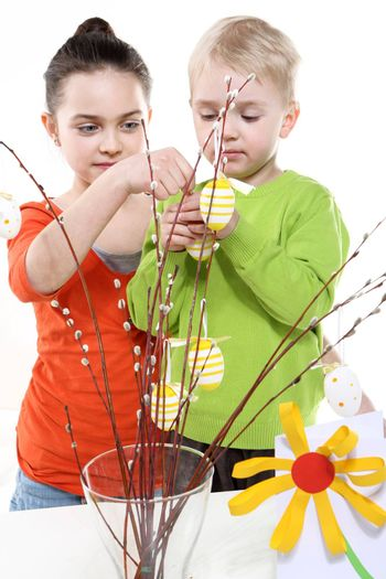 Children boy and girl painting Easter eggs