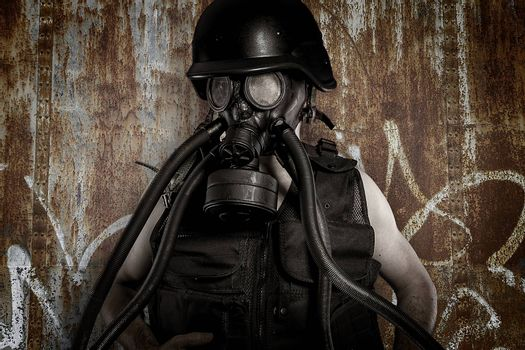 Man with gas mask over dirty texture iron wall
