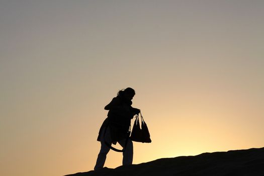 Woman walking uphill Silhouetted against Dusk Twilight