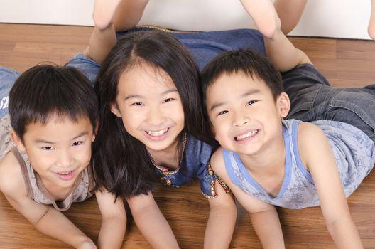Three happy children lying on floor
