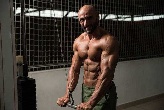 Mature Bodybuilder Exercise In The Gym - He Is Performing Two Arm Triceps Push Down