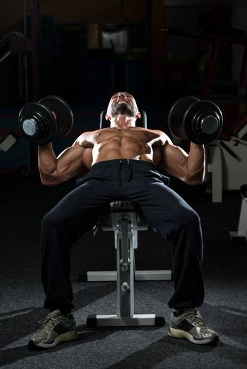 Mature Men Doing Dumbbell Incline Bench Press Workout In Gym