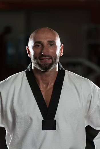 Portrait Of A Physically Fit Mature Man In Kimono With Black Belt